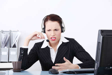 Front view of an beautiful business woman shouting through the headphones at work.