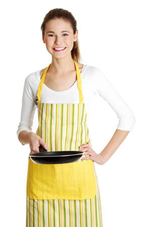 Front view portrait of a young smiling caucasian female teen dressed in apron, holding a frying pan in front of her, on white.