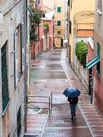 Man walking under the rain in a Genoa