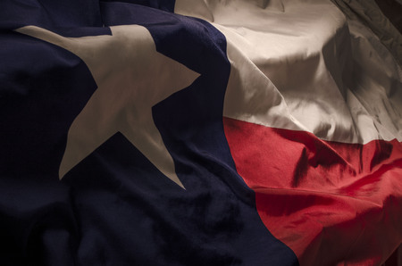 Photo pour close up view of the Texas Lone Star flag isolating the three separate colors and the single star amongst shadow, high lights and waves - image libre de droit