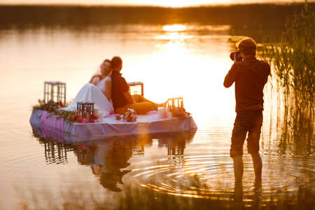 Photo pour Wedding photographer in action, taking a picture of the bride and groom sitting on the raft. Summer, sunset. - image libre de droit