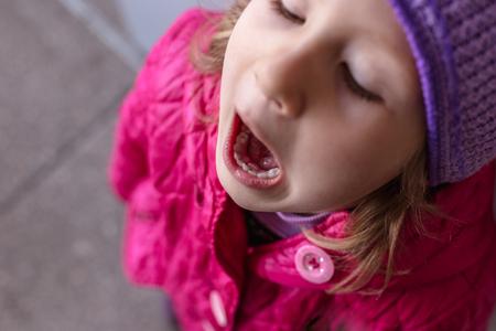 Foto de Adult permanent teeth coming in behind baby teeth: shark teeth. Opened mouth of little girl. - Imagen libre de derechos