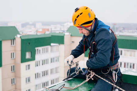 Foto de Industrial climber in uniform and helmet sitting on the roof preparing to the work in winter - Imagen libre de derechos