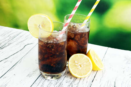 Photo pour Softdrink with ice cubes, lemon and straw in glass. - image libre de droit