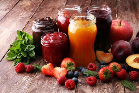 Foto de assortment of jams, seasonal berries, plums, mint and fruits  - Imagen libre de derechos