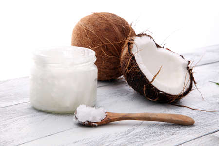 Photo for coconut and opened glass jar with fresh coconut oil on wooden background. - Royalty Free Image
