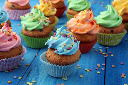 Photo pour Tasty cupcakes on wooden background. Birthday cupcake in rainbow colors - image libre de droit