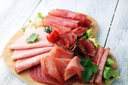 Foto de Food tray with delicious salami, pieces of sliced ham, sausage, tomatoes, salad and vegetable - Meat platter with selection - Imagen libre de derechos