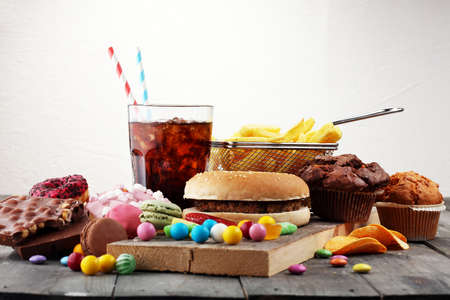 Foto per Unhealthy products. food bad for figure, skin, heart and teeth. Assortment of fast carbohydrates food.  - Immagine Royalty Free