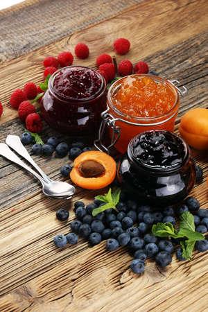 Foto de assortment of jams, seasonal berries, apricot, mint and fruits. marmalade or confiture - Imagen libre de derechos