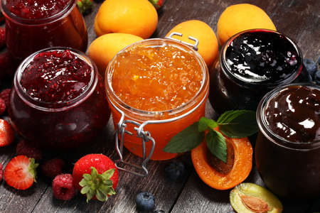 Photo for assortment of jams, seasonal berries, apricot, mint and fruits. marmalade or confiture - Royalty Free Image