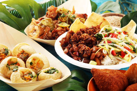 Photo for various street food with pani puri, chicken wings and coxinha on rustic background. balinese nasi campur and indian and brasilian street food - Royalty Free Image