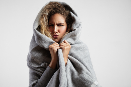 Foto de woman feeling freeze and wrap up in a blanket - Imagen libre de derechos