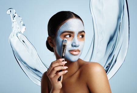 Photo pour woman put facial mask, water splash on a background - image libre de droit
