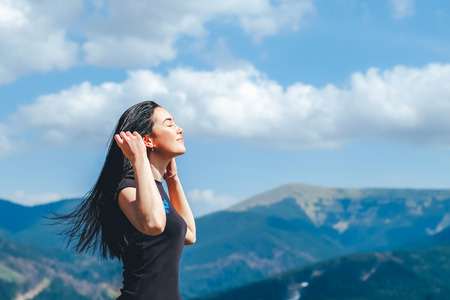 Photo for Long hair brunette girl on the top of the mountain enjoying fresh air - Royalty Free Image
