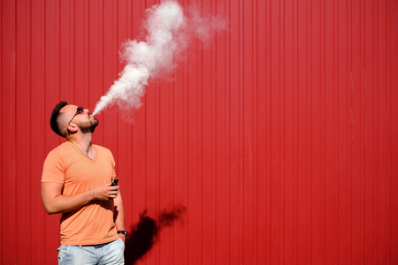 Photo for Vaper smoke electronic cigarette outdoor near wall - Royalty Free Image