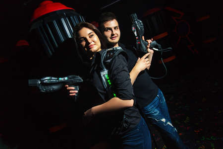Photo for Dark room girl and funny guy playing laser tag - Royalty Free Image