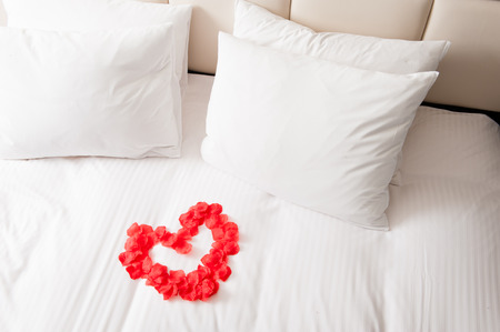 Photo pour Heart of red petals on bed - image libre de droit