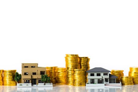 Foto de House model and lots of gold coins, white background - Imagen libre de derechos