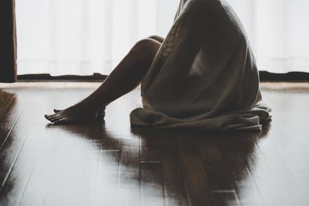 Foto de lonely woman sitting at the window - Imagen libre de derechos