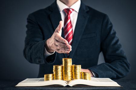 Photo pour businessman and gold coin placed on a book - image libre de droit