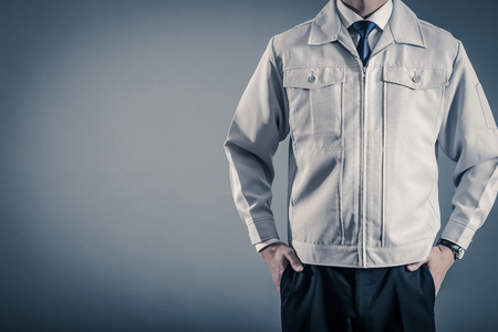 Photo for Men standing wearing work clothes with a gray background - Royalty Free Image