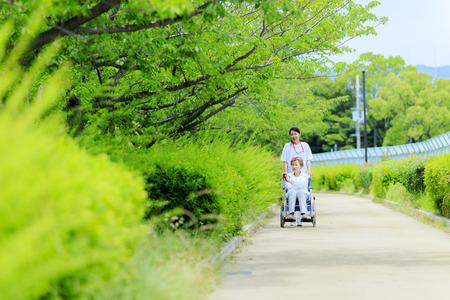 Photo pour Elderly female wheelchair and caregiver - image libre de droit