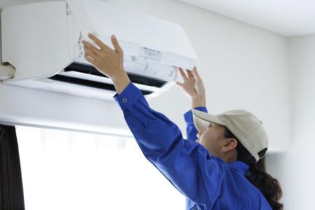 Photo pour woman to check the air conditioner - image libre de droit