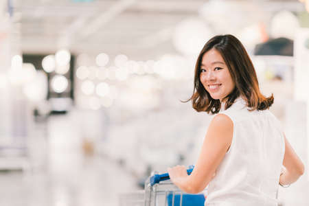 Foto de Beautiful young Asian woman smiling, with shopping cart, shopping center or department store scene, blur bokeh background with copy space, shopping or shopaholic concept - Imagen libre de derechos