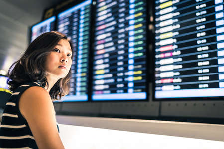 Photo for Beautiful Asian woman traveler at flight information screen in an airport, travel or time concept - Royalty Free Image