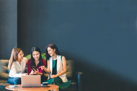 Photo pour Three beautiful Asian girls using smartphone and laptop, chatting on sofa at cafe with copy space, modern lifestyle with gadget technology or working woman on casual business concept - image libre de droit