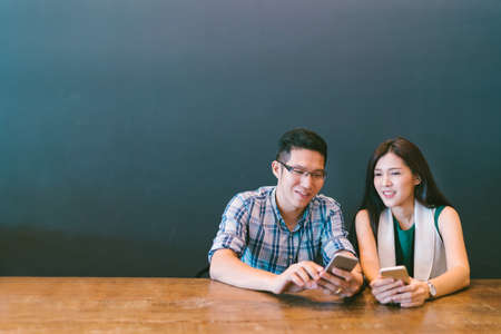 Foto de Young Asian couple or coworker using smartphone at cafe, modern lifestyle with gadget technology or casual business concept, with copy space - Imagen libre de derechos