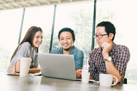 Foto de Group of young Asian business colleagues or college students using laptop in team casual discussion, startup project meeting or happy teamwork brainstorm concept, at coffee shop or modern office - Imagen libre de derechos