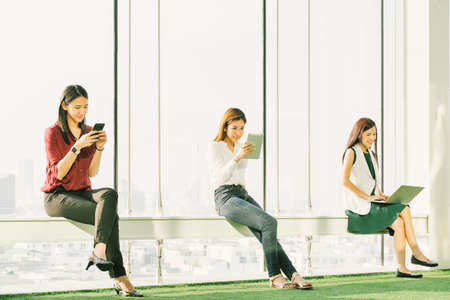 Foto de Three Asian girls using smartphone digital tablet and laptop computer in modern office at sunset. Modern lifestyle, information technology, internet gadget, or wireless online communication concept - Imagen libre de derechos