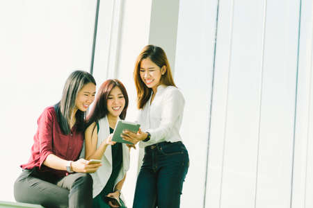 Foto de Three beautiful Asian girls using digital tablet together. Working woman or college students chatting at office with copy space. Modern lifestyle with gadget technology or casual business concept - Imagen libre de derechos