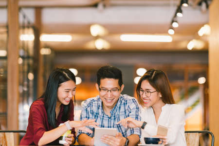 Photo pour Young Asian college students or coworkers using digital tablet together at coffee shop, diverse group. Casual business, freelance work at cafe, social meeting, or education concept - image libre de droit