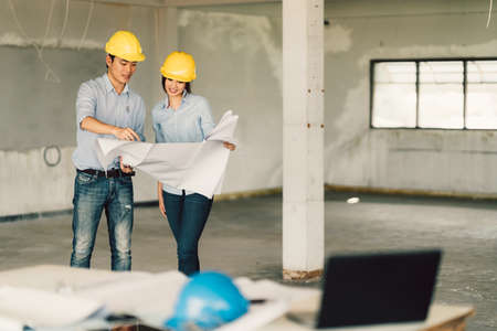 Foto de Young Asian engineers couple working on building blueprint at construction site. Civil engineering, industrial, or home renovation concept. With copy space - Imagen libre de derechos