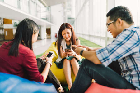 Foto de Three Asian college students or coworkers using smartphones together. Fun modern lifestyle, social network, or communication technology gadget concept, focus on middle girl, depth of field effect - Imagen libre de derechos