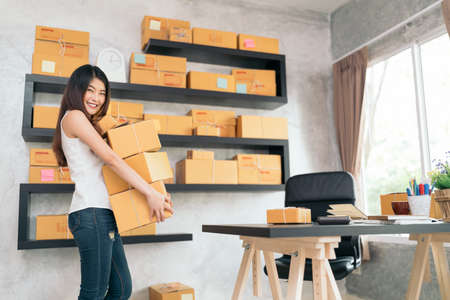 Foto de Young Asian small business owner carrying product boxes at home office, online marketing packaging and delivery scene, startup SME entrepreneur or freelance woman working at home concept - Imagen libre de derechos