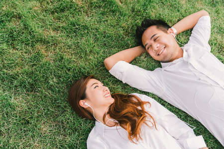 Foto de Young Asian lovely couple or college students lying down on the grass together, listening to music, top view with copy space. Love, relationship, wedding, or relaxing casual lifestyle concept - Imagen libre de derechos