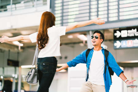 Photo pour Asian girl picking up her boyfriend at airport's arrival gate, welcomes back home from studying or working abroad. Young couple love and hug, honeymoon, or traveling concept - image libre de droit