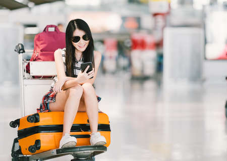 Foto de Young Asian girl using smartphone, waiting for flight at airport, sitting on baggage trolley or luggage cart. Mobile communication technology or travel abroad concept, with copy space - Imagen libre de derechos