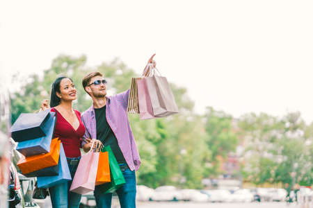 Foto für Multiethnic couple with shopping bags, man pointing at copy space on sky. Love, casual lifestyle, or shopaholic concept - Lizenzfreies Bild