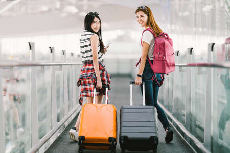 Foto de Two happy Asian girls traveling abroad together, carrying suitcase luggage in airport. Air travel or holiday vacation concept - Imagen libre de derechos
