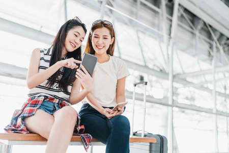 Photo pour Two happy Asian girls using smartphone checking flight or online check-in at airport together, with luggage. Air travel, summer holiday, or mobile phone application technology concept - image libre de droit
