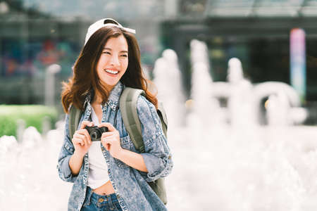 Photo pour Young beautiful Asian backpack traveler woman using digital compact camera and smile, looking at copy space. Journey trip lifestyle, world travel explorer or Asia summer tourism concept - image libre de droit