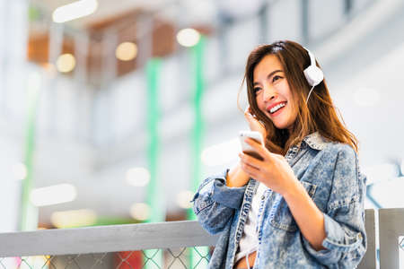 Photo pour Beautiful young Asian girl listen to music using smartphone and headphone smile at copy space. Modern teenager lifestyle, college student hobby, youth culture or mobile phone gadget technology concept - image libre de droit