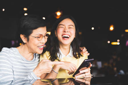 Photo pour Asian mother and daughter laughing and smiling on a selfie or photo album, using smartphone together at restaurant or cafe, with copy space. Family love, holiday activity, or modern lifestyle concept - image libre de droit