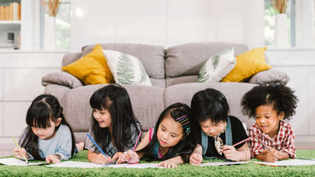 Photo pour Group of five multi-ethnic young cute preschool kids, boy and girls happy studying or drawing together at home or school. Children education, youth culture lifestyle, or fun learning activity concept - image libre de droit