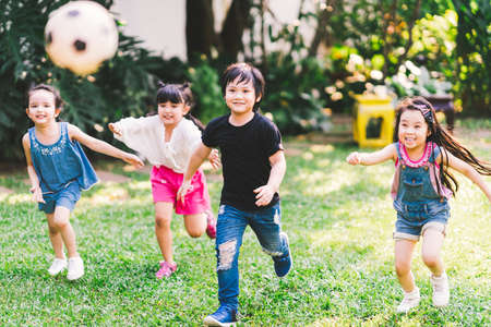 Foto de Asian and mixed race happy young kids running playing football together in garden. Multi-ethnic children group, outdoor sport exercising, leisure game activity, or childhood fun lifestyle concept - Imagen libre de derechos